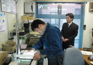 04_検査装置の準備をする西川さん